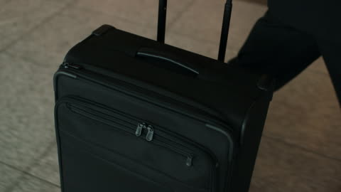 vídeos de stock, filmes e b-roll de high angle shot of suitcase pushed in airport - mala de rodinhas
