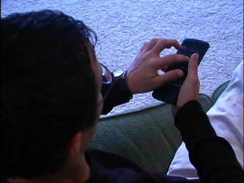 high angle shot of teen boy holding and pressing buttons on television remote control. - endast en tonårspojke bildbanksvideor och videomaterial från bakom kulisserna