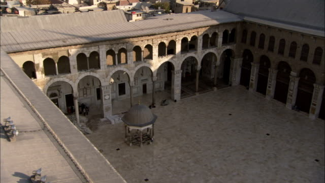 A high angle shot of the courtyard of the Umayyad Mosque and the surrounding city of Damascus. Available in HD.