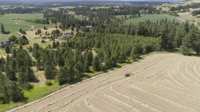 high angle shot of tractor raking hay field - bailing hay stock videos & royalty-free footage