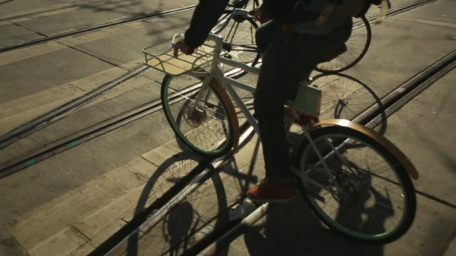 vidéos et rushes de ms ts tu slo mo high angle shot of two bikes crossing over metro train with tracks sun shining casting shadows and biker down street / san francisco, california, united states - composant électrique