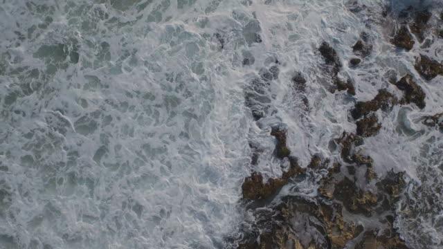 High angle shot of waves crashing on coast