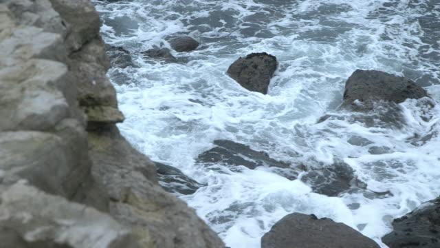 High angle shot of waves crashing onto rocks on the Dorset coast.