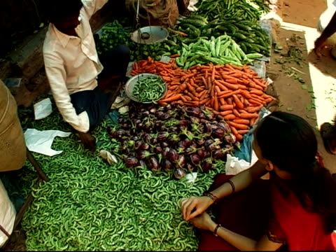 high angle shot of woman pushing peas onto scale held by vendor at outdoor market / vendor weighing peas / zoom in to woman holding plastic bag open as vendor slides peas into bag / bangalore, karnataka, india - market trader stock videos & royalty-free footage