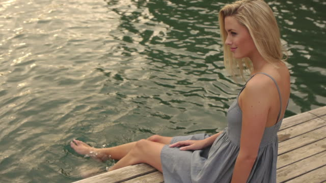vídeos de stock, filmes e b-roll de high angle shot of woman sitting on dock/marbella region, spain - só mulheres jovens