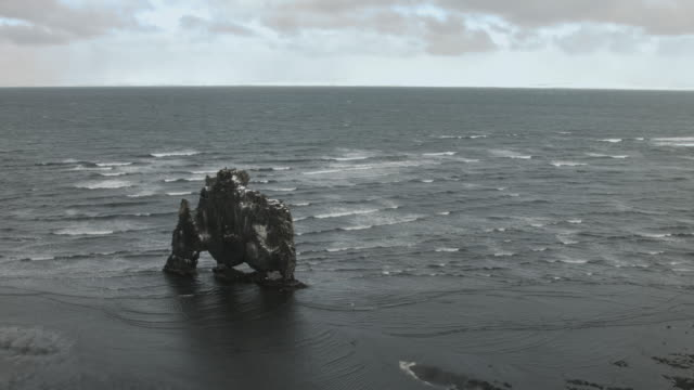 high angle shot over a basalt sea stack on the coast of iceland. - basalt stock videos & royalty-free footage