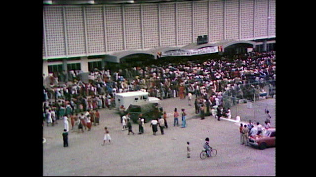 high angle shot, panning right over the crowds assembling outside jamaica's national arena for bob marley's state funeral ceremony; 1981. - ボブ・マーリー点の映像素材/bロール