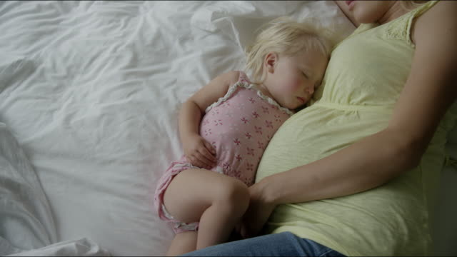 High angle slow motion close up shot of pregnant mother and daughter sleeping on bed / Cedar Hills, Utah, United States