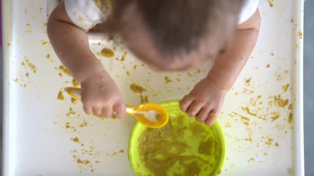 vídeos de stock, filmes e b-roll de vídeo hd do movimento lento do ângulo elevado do bebé que come o alimento na cadeira de alimentação - comida de bebê