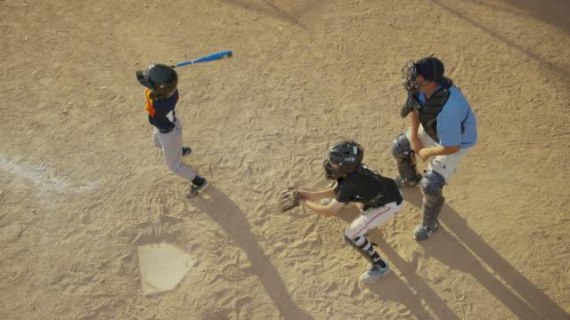 High angle slow motion medium shot of baseball batter hitting ball / American Fork, Utah, United States