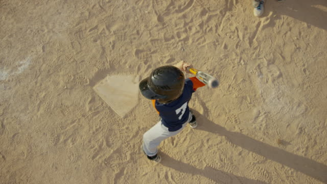High angle slow motion medium shot of baseball player at home plate / American Fork, Utah, United States