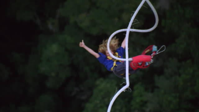 vídeos y material grabado en eventos de stock de high angle slow motion shot of a person bungee jumping with their arms outstretched to the side, and giving a thumbs up sign as she come up - puenting