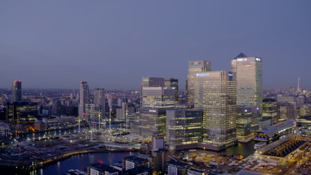 High angle, slow pan shot of Canary Wharf and London Looking west at sunset