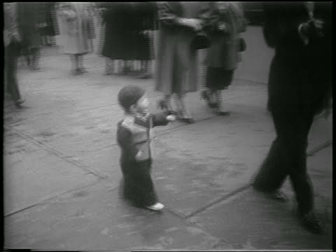 vidéos et rushes de b/w 1952 high angle pan small boy in cap walking on sidewalk looking at camera / easter / nyc / newsreel - 1952