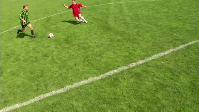 high angle soccer player dribbling ball downfield / being tackled by another player / fouled player pushing and fighting with opponent / teammate coming to his defense - kleine personengruppe stock-videos und b-roll-filmmaterial