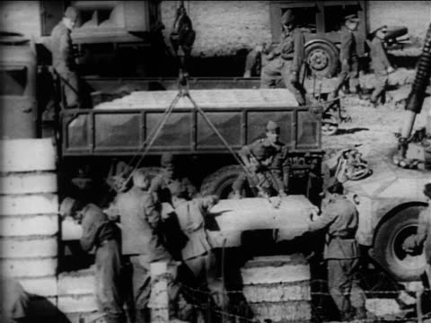 high angle soldiers guiding cement slab being lowered by crane / berlin wall construction - 1961 stock videos & royalty-free footage