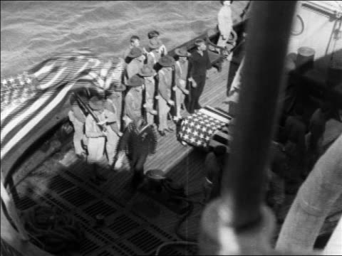 high angle soldiers standing near coffin draped with us flag on ship / newsreel - anno 1925 video stock e b–roll