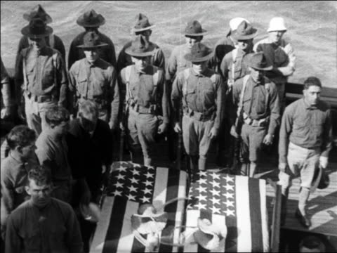 high angle soldiers standing near two coffins draped with us flags on ship / newsreel - anno 1925 video stock e b–roll