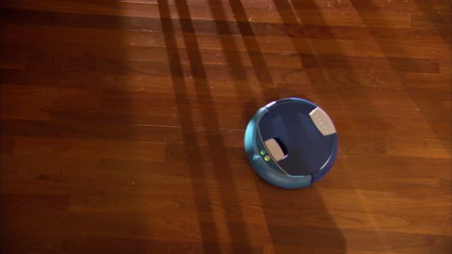 High Angle static - A small robotic vacuum cleaner sweeps a hardwood floor.