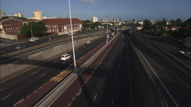 high angle static - heavy traffic zips along multi-lane freeways in durban, south africa. / durban, south africa - durban stock videos and b-roll footage