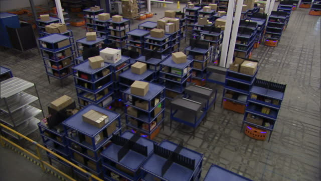 vídeos de stock e filmes b-roll de high angle static - robots move crates in a warehouse. / woburn, massachusetts, usa - automatizado