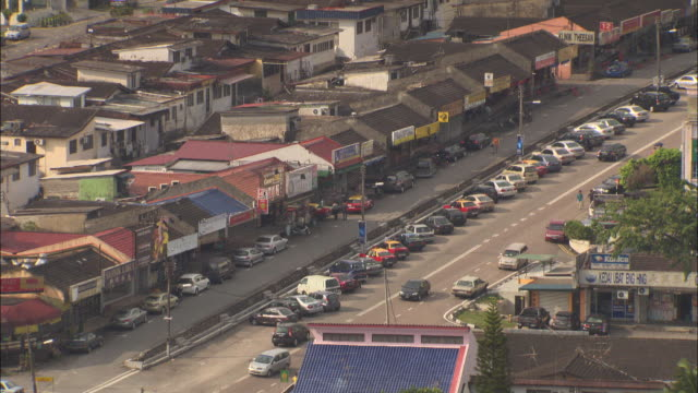 high angle static - traffic moves along a street lined with cars and colorful buildings. / malaysia - centro commerciale suburbano video stock e b–roll