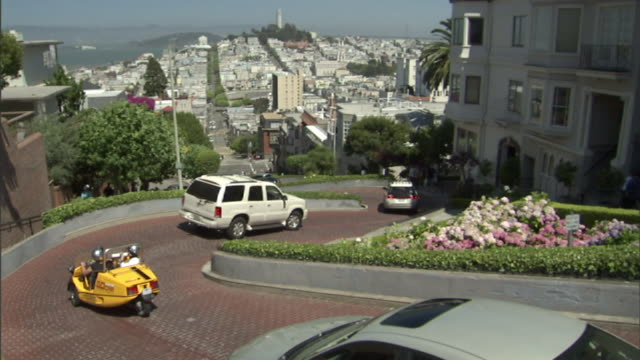 high angle static - traffic moves slowly along curving neighborhood streets in san francisco. / san francisco, california, usa - lombard street san francisco stock videos & royalty-free footage