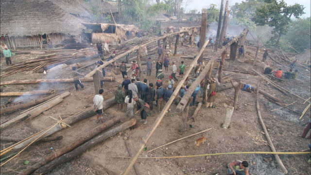 vidéos et rushes de high angle static - villagers construct a new building from log poles in ethiopia. / india - cabane structure bâtie