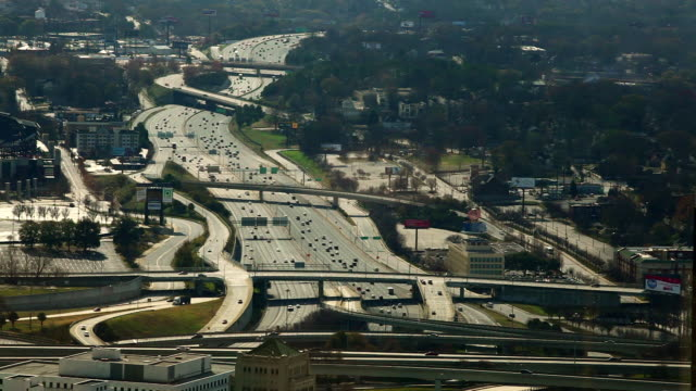 A high angle, static, wide shot of cars flowing on the freeway in Atlanta, Georgia.
