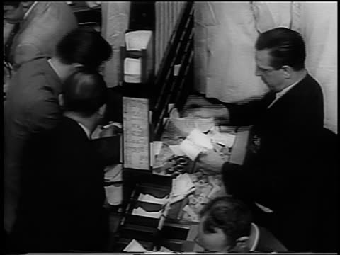 high angle stockbrokers sorting out pieces of paper in busy ny stock exchange / newsreel - 1962年点の映像素材/bロール