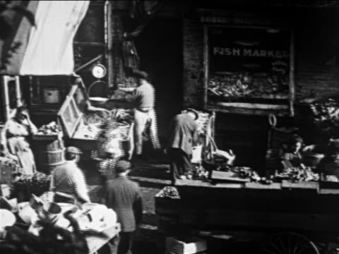 B/W 1913 high angle street vendors + passersby in front of fish market / Lower East Side, NYC