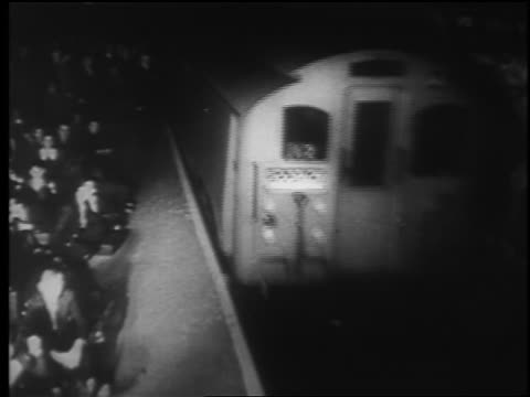 vídeos y material grabado en eventos de stock de b/w 1940 high angle subway train pulling into station with crowd sitting on floor / london blitz / educational - 1940