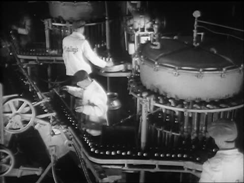 b/w 1933 high angle three men watching bottles of beer moving on conveyor in factory - bottling plant stock videos & royalty-free footage