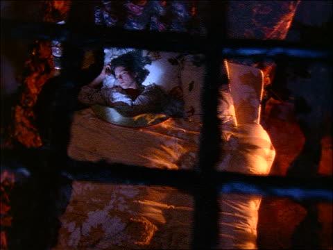vídeos y material grabado en eventos de stock de high angle thru skylight of woman sleeping restlessly in bed - onírico