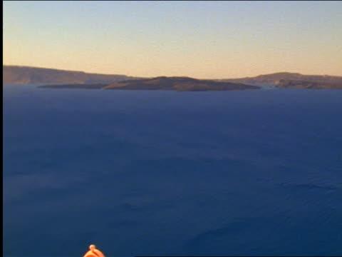 high angle tilt down pan blue sea to blue dome of church overlooking sea / oia, santorini island, greece - イア点の映像素材/bロール
