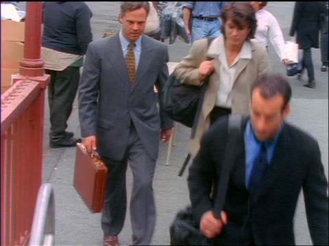 stockvideo's en b-roll-footage met high angle tilt down businesspeople entering subway station / new york city - 1990