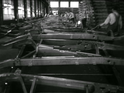 vídeos de stock e filmes b-roll de b/w 1936 high angle tilt down car frames moving on conveyor belt on assembly line in chevrolet factory - 1930