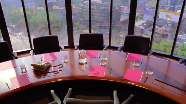 vidéos et rushes de high angle tilt down conference table set up for meeting / windows + city in background - salle de réunion