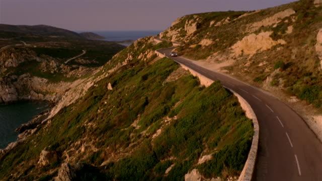 High angle tilt down convertible driving along winding mountain road / Corsica