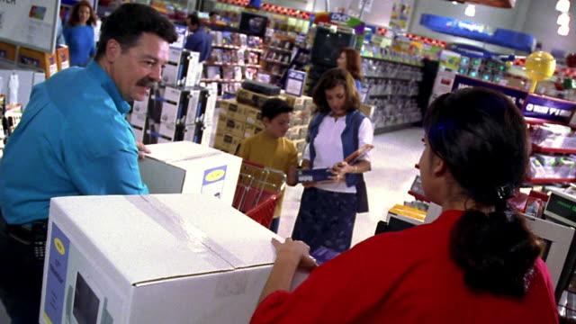 vídeos de stock, filmes e b-roll de high angle tilt down ms hispanic man placing computer boxes on counter at checkout with female cashier - loja de produtos eletrônicos