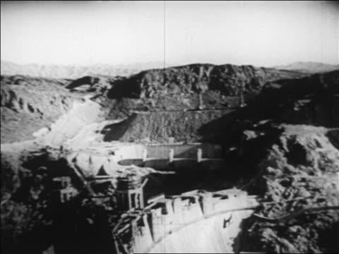 b/w 1936 high angle tilt down hoover dam under construction / nevada / newsreel - hoover staudamm stock-videos und b-roll-filmmaterial