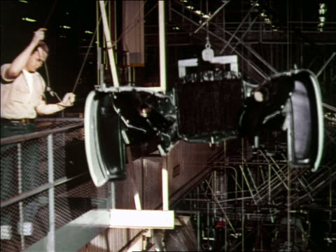1951 high angle tilt down man lowering car body piece to assembly line below on crane / chevrolet - 1951 stock videos & royalty-free footage