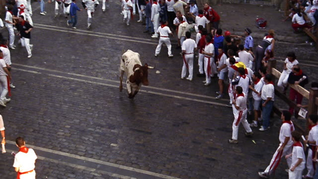 high angle PAN tilt down people running away from bull on city street / Running of the Bulls / Pamplona, Spain