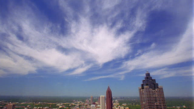 high angle tilt down wide shot from clouds in sky to atlanta skyline / georgia - schwenk nach unten stock-videos und b-roll-filmmaterial