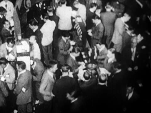 high angle tilt up busy traders on floor of new york stock exchange / wall street, nyc / newsreel - 1920 1929 stock-videos und b-roll-filmmaterial
