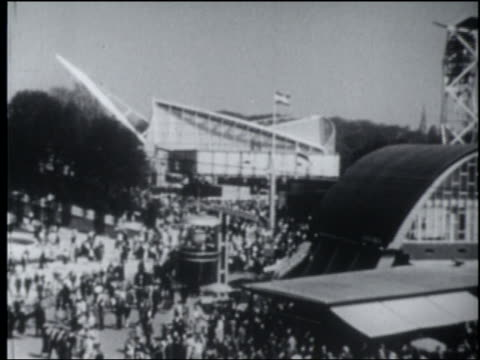 b/w 1958 high angle tilt up pan cable cars moving above crowded brussels world's fair - 1958 stock videos & royalty-free footage