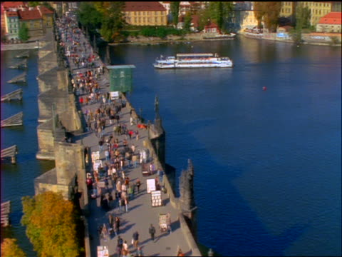 high angle tilt up crowd on charles bridge to skyline of prague / czech republic - charles bridge stock videos & royalty-free footage