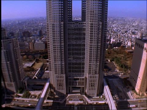 vídeos de stock e filmes b-roll de high angle tilt up from bottom to top of skyscraper office building / shinjuku / tokyo - 1997
