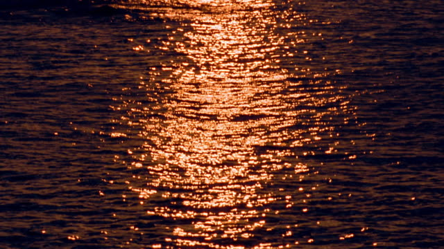 High angle tilt up from medium shot rippling water with reflection from sunset to wide shot silhouetted hilly coast in background / Hawaii