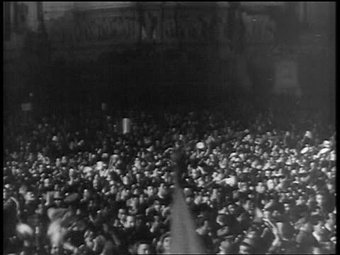 stockvideo's en b-roll-footage met b/w 1938 high angle tilt up large crowd cheering at nighttime rally / mussolini / rome - 1938